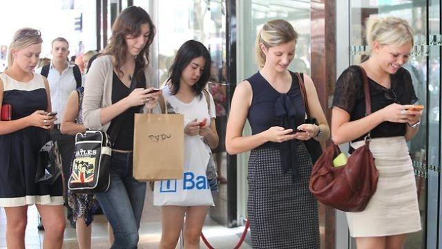 Resultado de imagen de El cualquier calle de una gran ciudad, los jóvenes caminan con el móvil en la mano